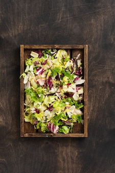 Wymieszaj świeże liście rukoli, sałaty, szpinaku, buraków na sałatkę w drewnianym pudełku na drewnianym rustykalnym.