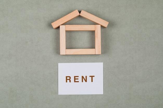 Wynajem domu koncepcja z drewnianych klocków, karteczkę na szarym tle płaskiej leżał.