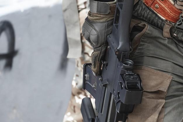 Wynajęty żołnierz trzyma w ręku opuszczony karabin.