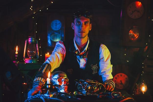Wynalazca steampunk w garniturze przy stole z różnymi mechanizmami