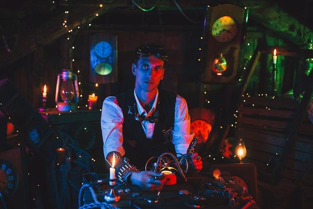 Wynalazca w steampunkowym garniturze naprawia fantastyczny mechanizm przy stole w warsztacie zegarmistrzowskim
