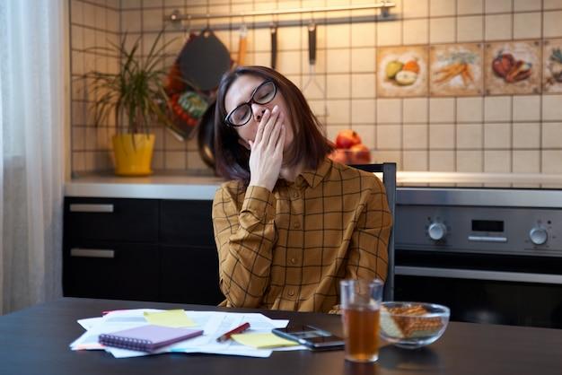 Wyobraź sobie zmęczone ziewające kobiety w kuchni ubrane w koszulę i okulary, t