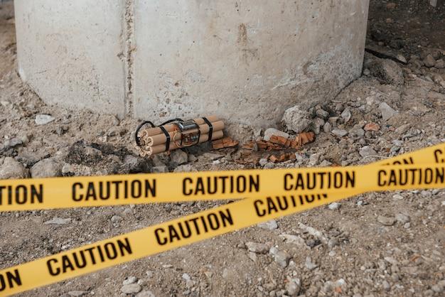 Wypadek pod mostem. niebezpieczny materiał wybuchowy leżący na ziemi. z przodu żółta taśma ostrzegawcza