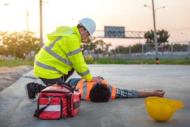 Wypadek przy pracy robotników budowlanych, podstawowa pierwsza pomoc i szkolenie z rko na świeżym powietrzu.