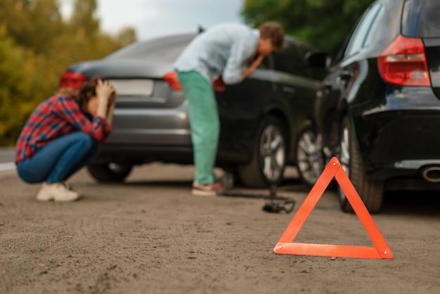 Wypadek samochodowy na drogach, kierowców płci męskiej i żeńskiej. wypadek samochodowy, znak stopu awaryjnego. uszkodzony samochód lub uszkodzony pojazd, kolizja samochodowa na autostradzie