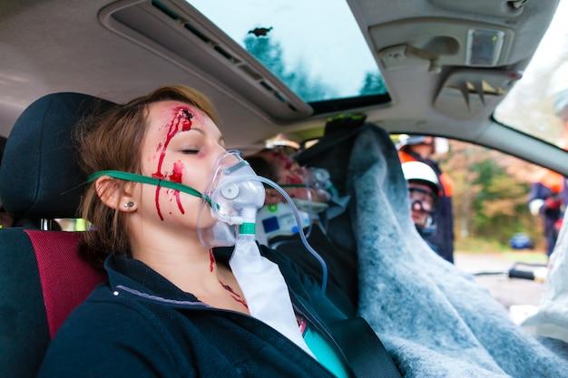 Wypadek samochodowy - ofiara w rozbitym pojeździe otrzymującym pierwszą pomoc
