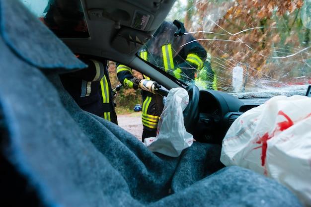 Wypadek samochodowy, ofiary w rozbitym pojeździe otrzymujące pierwszą pomoc