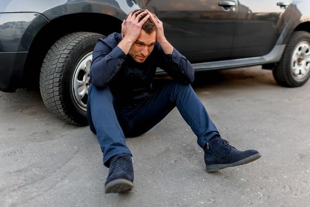Wypadek samochodowy, wypadek drogowy, zrozpaczony mężczyzna siedzi przy kole swojego samochodu. położył ręce na głowie. czuje panikę i wściekłość