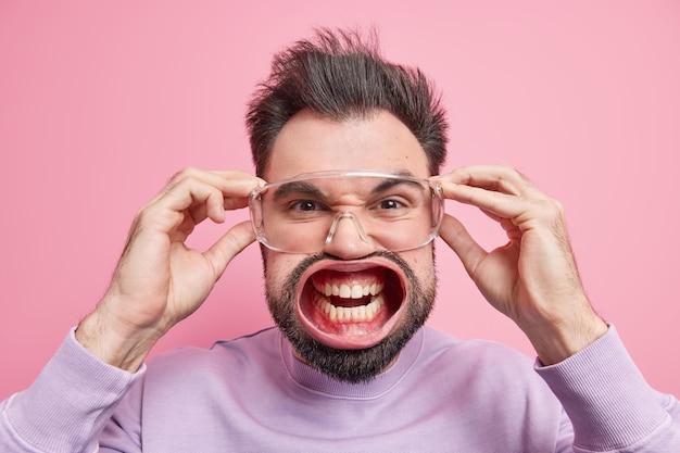 Wypalenie emocjonalne. strzał w głowę brodatego dorosłego mężczyzny czuje ogromny nacisk, krzyczy, gniewnie zaciska zęby, trzyma ręce na przezroczystych okularach, mruży oczy, wyraża złość