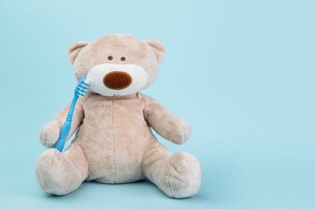 Wypchane zwierzę niedźwiedź szczoteczką do zębów na białym tle na niebieskiej powierzchni. motyw dentysty dla dzieci