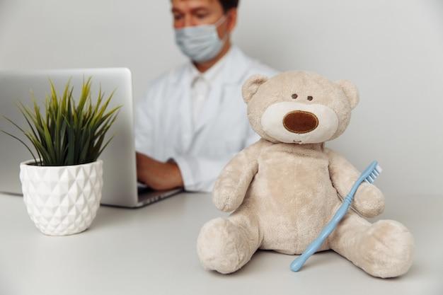 Wypchany miś ze szczoteczką do zębów w gabinecie dentystycznym. koncepcja opieki zdrowotnej dziecka.