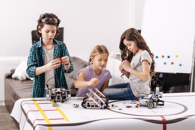 Wypełnianie naszych obowiązków. śliczne zaangażowane pracowite dzieciaki siedzące w laboratorium robotyki i testujące cyber-urządzenia podczas lekcji przedmiotów ścisłych