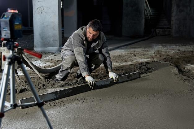 Wypełnianie posadzki betonem, jastrych i wyrównywanie posadzki przez pracowników budowlanych. posadzki gładkie z mieszanki cementowej, betonowanie przemysłowe