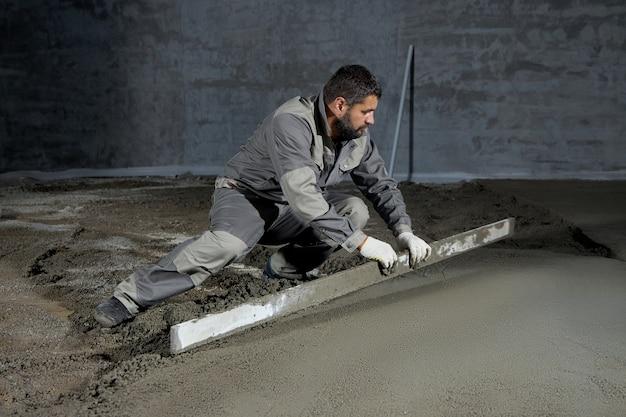 Wypełnianie posadzki betonem, wylewką i wyrównywaniem przez pracowników budowlanych