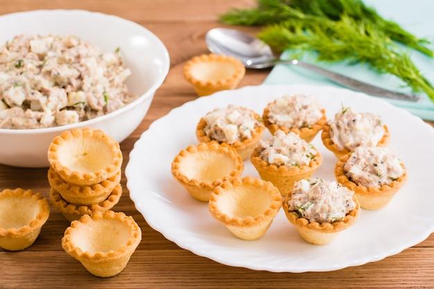 Wypełnianie tartaletów sałatką z saury w puszkach i jajkami