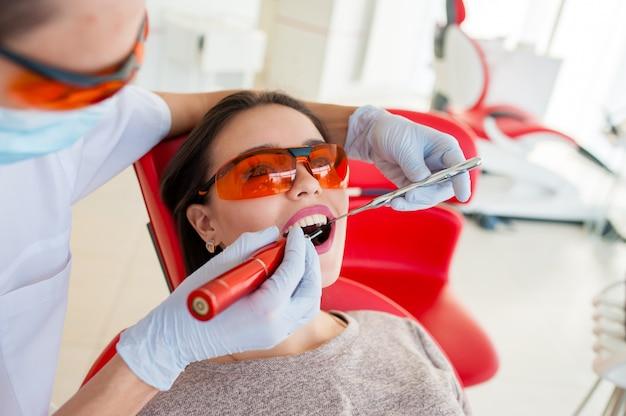 Wypełnianie zębów u dziewczyny w stomatologii.