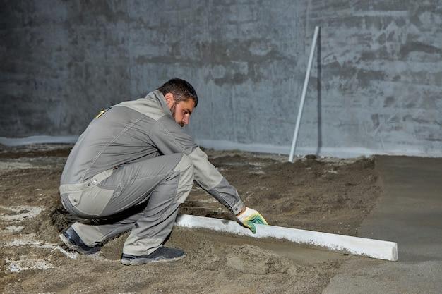 Wypełnienie podłogi betonem, wylewką oraz wyrównanie podłogi przez pracowników budowlanych. gładkie podłogi wykonane z mieszanki cementu