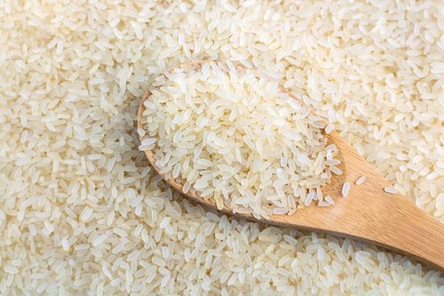 Wypełniona drewniana łyżka z bliska niegotowane parboiled biały ryż. długie ziarna, widok z góry ekologicznej naturalnej zdrowej żywności.