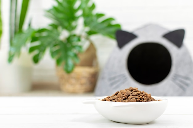 Wypełniona miska suchej karmy na podłodze w pobliżu domku dla kotów. zdrowie kotów domowych, zbilansowane żywienie i pielęgnacja zwierząt domowych.