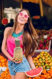 Wypełniona radością letnia dziewczyna bawi się na targu owoców tropikalnych. trzyma anany, kawałek arbuza i uśmiecha się