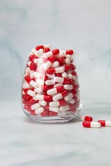 Wypełnione szkło z kapsułkami, tabletki na leki. leki lub witaminy, różne tabletki leków farmaceutycznych