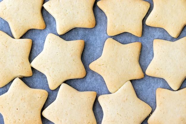 Wypiekane kruche ciasteczka w formie gwiazdek na blasze wyłożonej papierem do pieczenia