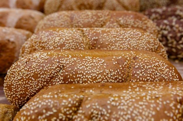 Wypieki, bochenki chleba z sezamem na półce lub w gablocie w piekarni lub sklepie