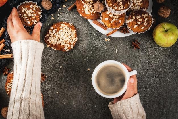 Wypieki jesienno-zimowe. wegańskie jedzenie. zdrowe ciasteczka, babeczki z orzechami, jabłka, płatki owsiane. przytulna atmosfera, ciepły koc, dziewczyna pije kawę, ręce w obrazie. stół z ciemnego kamienia. widok z góry