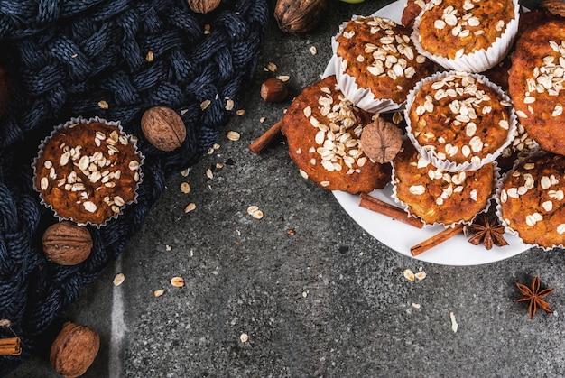 Wypieki jesienno-zimowe. wegańskie jedzenie. zdrowe domowe ciasteczka do pieczenia, babeczki z orzechami, jabłka, płatki owsiane. przytulna domowa atmosfera, ciepły koc, składniki. stół z ciemnego kamienia. widok z góry