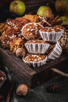 Wypieki jesienno-zimowe. wegańskie jedzenie. zdrowe domowe ciasteczka do pieczenia, babeczki z orzechami, jabłka, płatki owsiane. przytulna domowa atmosfera, ciepły koc, składniki. stół z ciemnego kamienia.