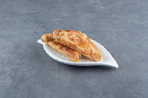 Wypieki w kształcie trójkąta wypełnione serem na białym talerzu.