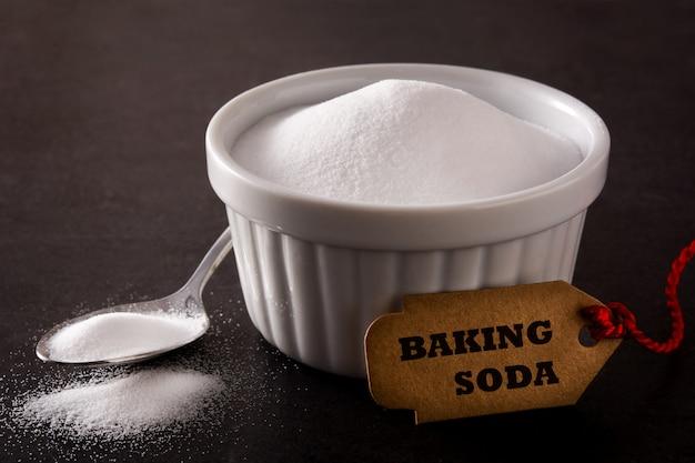 Wypiekowa soda w białym pucharze na czarnym tle
