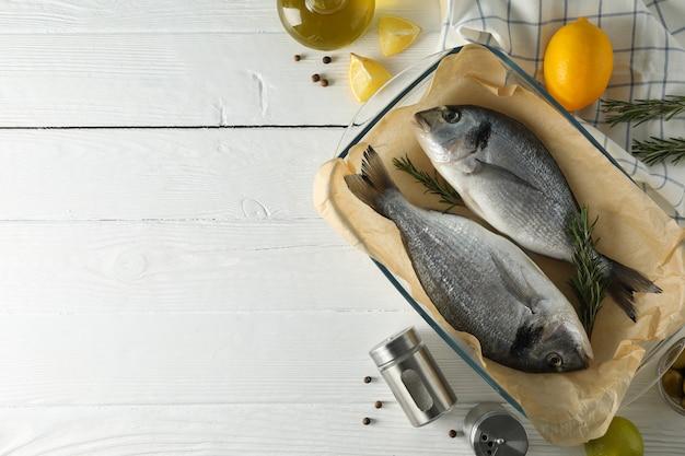 Wypiekowa taca z dorado ryba i kulinarnymi składnikami na drewnianym tle, odgórny widok