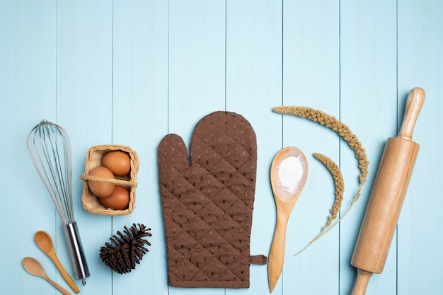 Wypiekowego wyposażenia narzędzia na błękitny drewnianym. jajko, mąka, cukier, masło, orzechy na niebiesko