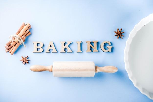 Wypiekowy pojęcie z białym pieczenia naczyniem, toczna szpilka, pikantność dla piec, na bławym tle, odgórnego widoku kopii przestrzeń