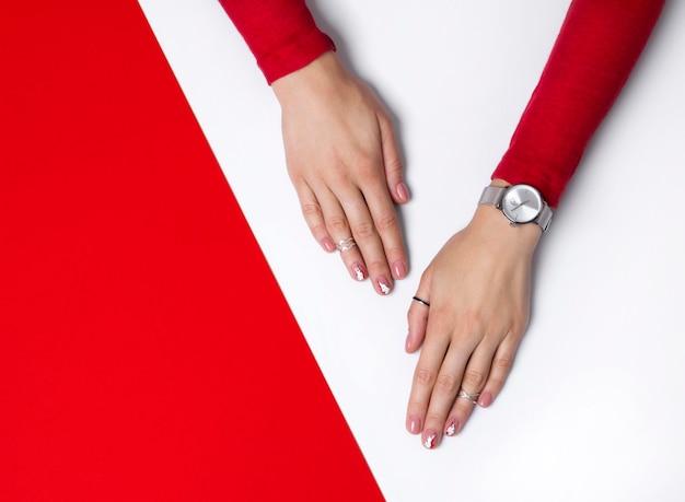 Wypielęgnowana ręka kobiety przy stole białym i czerwonym
