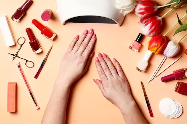 Wypielęgnowane dłonie i sprzęt do manicure. młoda kobieta ręce z pięknym manicure na biurku koralowy kolor z przyrządami do manicure i tulipanów. wiosenny manicure. salon paznokci i spa. widok z góry.