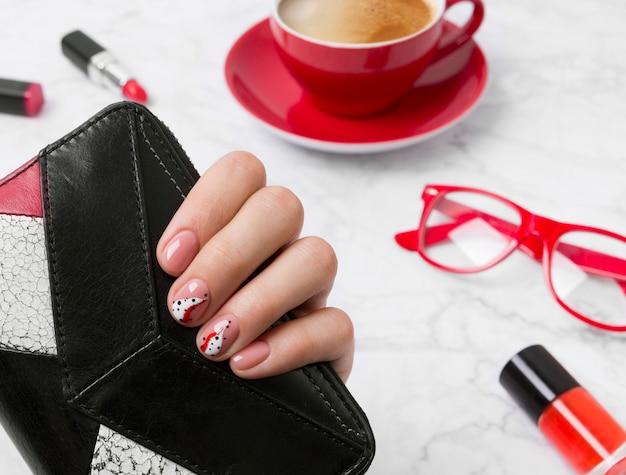 Wypielęgnowane kobiety ręki trzymającej torebkę przy biurowym stole.