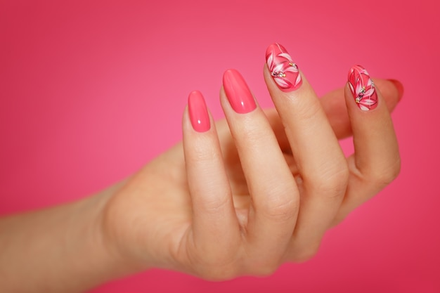 Wypielęgnowane paznokcie kobiety z różowym zdobieniem z kwiatami. manicure nailart.