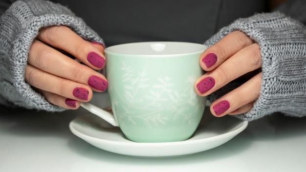 Wypielęgnowane paznokcie z filiżanką kawy
