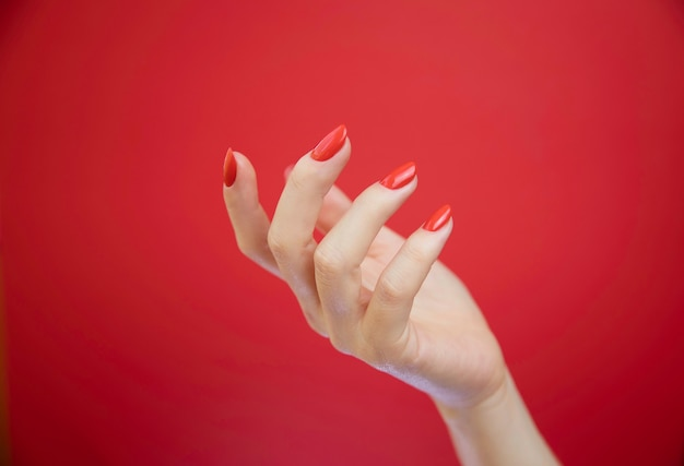 Wypielęgnowane ręce kobiety na czerwonym tle.