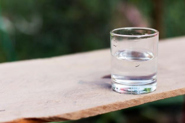 Wypij szklankę wody na drewnianej podłodze.