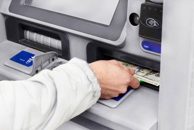 Wypłata gotówki w dolarach z bankomatu.
