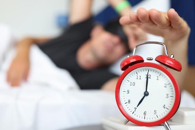 Wypoczęty mężczyzna sięga po przycisk zegarka, aby wyłączyć codzienny alarm i obudzić koncepcję czasu budzenia
