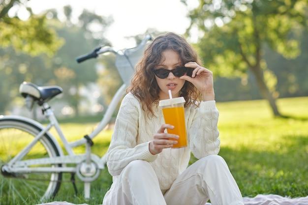 Wypoczynek. dziewczyna w bieli siedząca na trawie w parku
