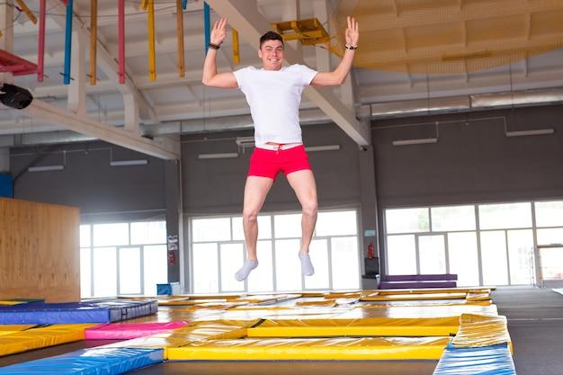 Wypoczynek, gry sportowe i zainteresowania - zabawny młody człowiek na trampolinie w fly parku.