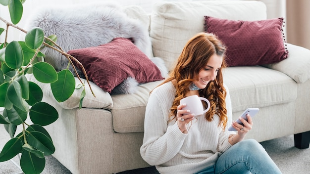 Wypoczynek kobiety. przytulna domowa atmosfera. zawartość młoda dama siedzi na podłodze z telefonu przeglądania kubka.