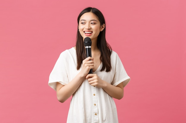 Wypoczynek, ludzie emocje i koncepcja stylu życia. wesoła uśmiechnięta azjatka w karaoke, ciesząc się weekendami, śpiewając piosenkę w mikrofonie, wykonując stójkę, stojąc na różowym tle.