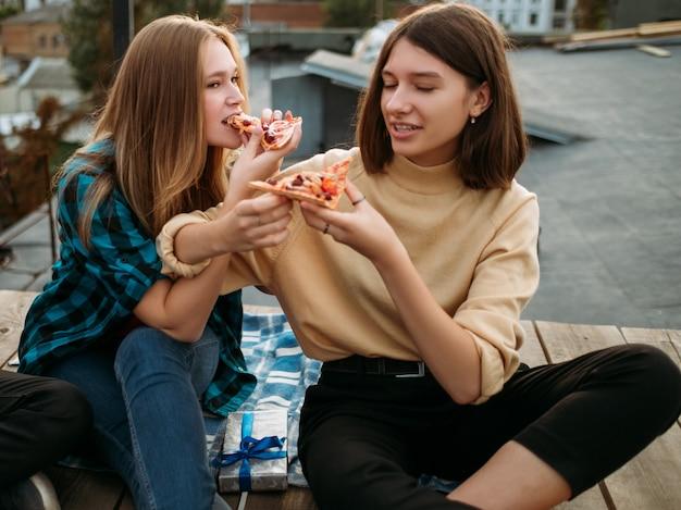 Wypoczynek nastolatków. czas zjeść pyszne jedzenie. głodni młodzi ludzie próbują plasterków pizzy. zbilansowane odżywianie nie jest dla młodzieży