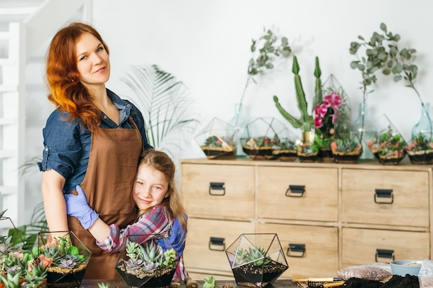 Wypoczynek rodzinny. miłość i pomoc. szczęśliwa matka i córka stojąca obejmując w przydomowym ogrodzie z sukulentami.